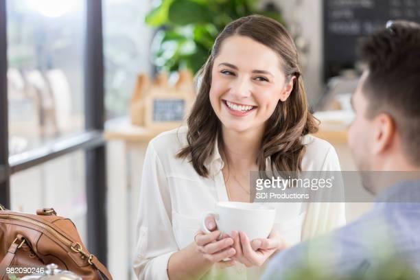 若い女性彼女のコーヒー ショップで悪戯っぽく笑顔 - 恥ずかしがり ストックフォトと画像