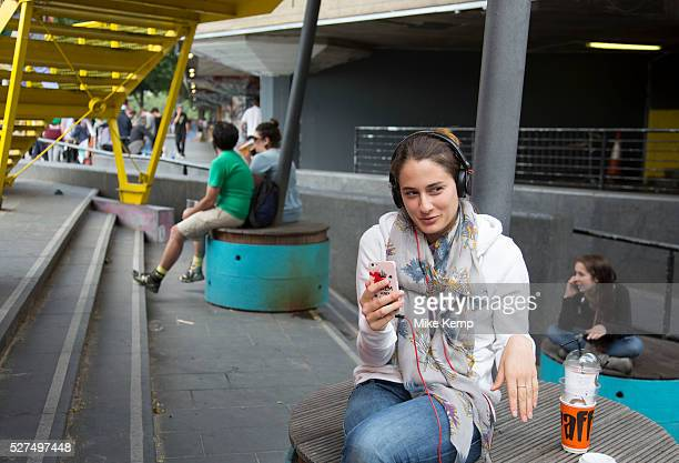 Young woman smiles while she enjoys a Facetime call with a friend on her smartphone She is happily in her own world smiling and laughing and making...