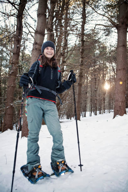 A young woman smiles while snowshoeing through the woods.