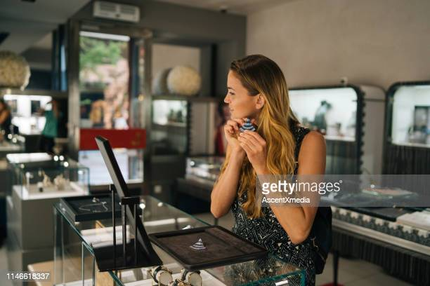 young woman smiles while trying on jewellery - jewelry store stock pictures, royalty-free photos & images
