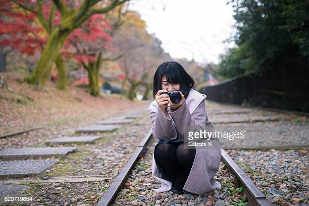 Young woman smiley taking pictures on dead railroad track