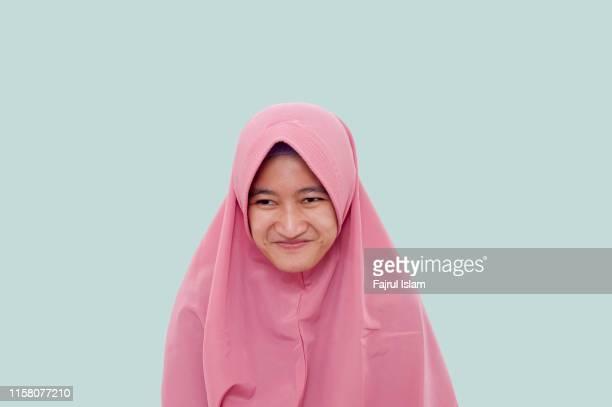 young woman smiling against light blue background - alleen tieners stockfoto's en -beelden
