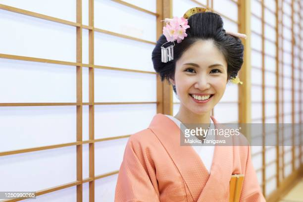 young woman smiling against paper screen, wearing kimono - ボン ストックフォトと画像