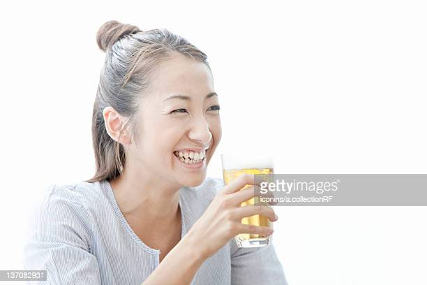 Young woman smiling and holding a glass of beer, Tokyo Prefecture, Japan