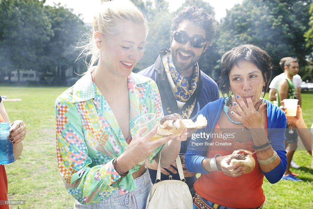 young woman smiling and holding a hamburger : Foto de stock