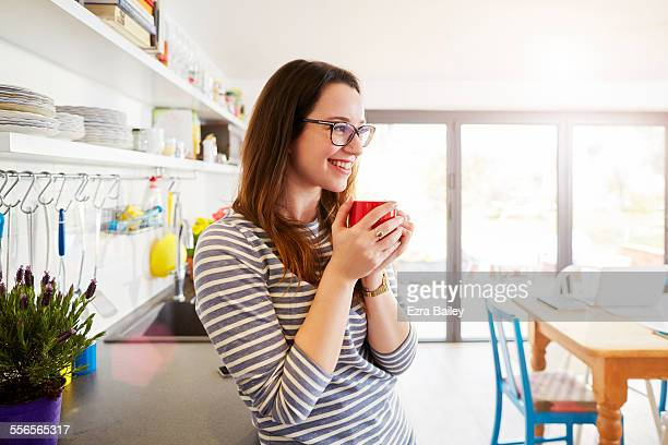 young woman smiling and holding coffee in kitchen - home ownership stock pictures, royalty-free photos & images