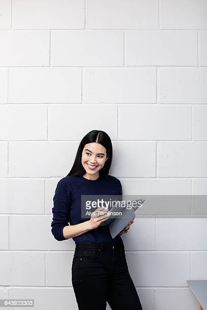 young woman smiling and holding tablet - leanincollection stock pictures, royalty-free photos & images