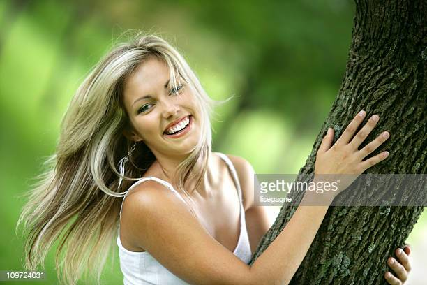 Young Woman Smiling and Holding Tree