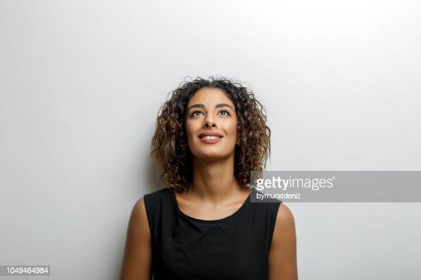 young woman smiling and looking up - looking up stock pictures, royalty-free photos & images