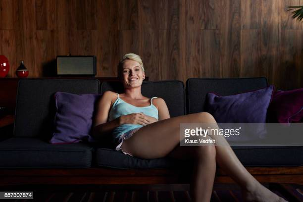 young woman smiling and sitting in couch - one young woman only stock pictures, royalty-free photos & images