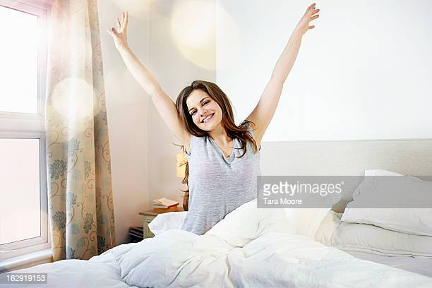 young woman smiling and stretching in bed - waking up stock pictures, royalty-free photos & images