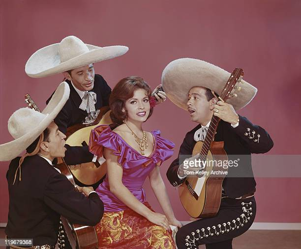 young woman smiling and surrounded by musician - mexican culture stock photos and pictures