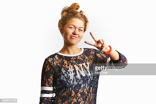 Young woman smiling and throwing peace sign