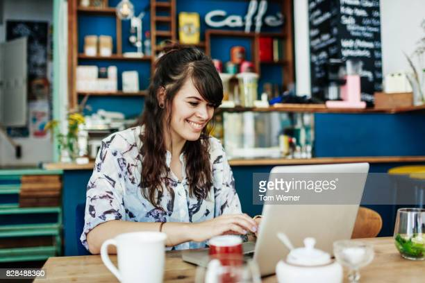 Young Woman Smiling As She Messages Friends On Laptop In Cafe