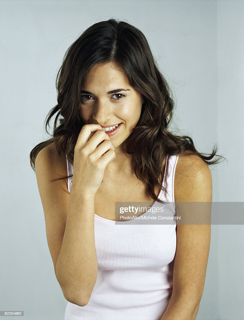 Young woman smiling at camera, biting fingernail, portrait : Stock Photo