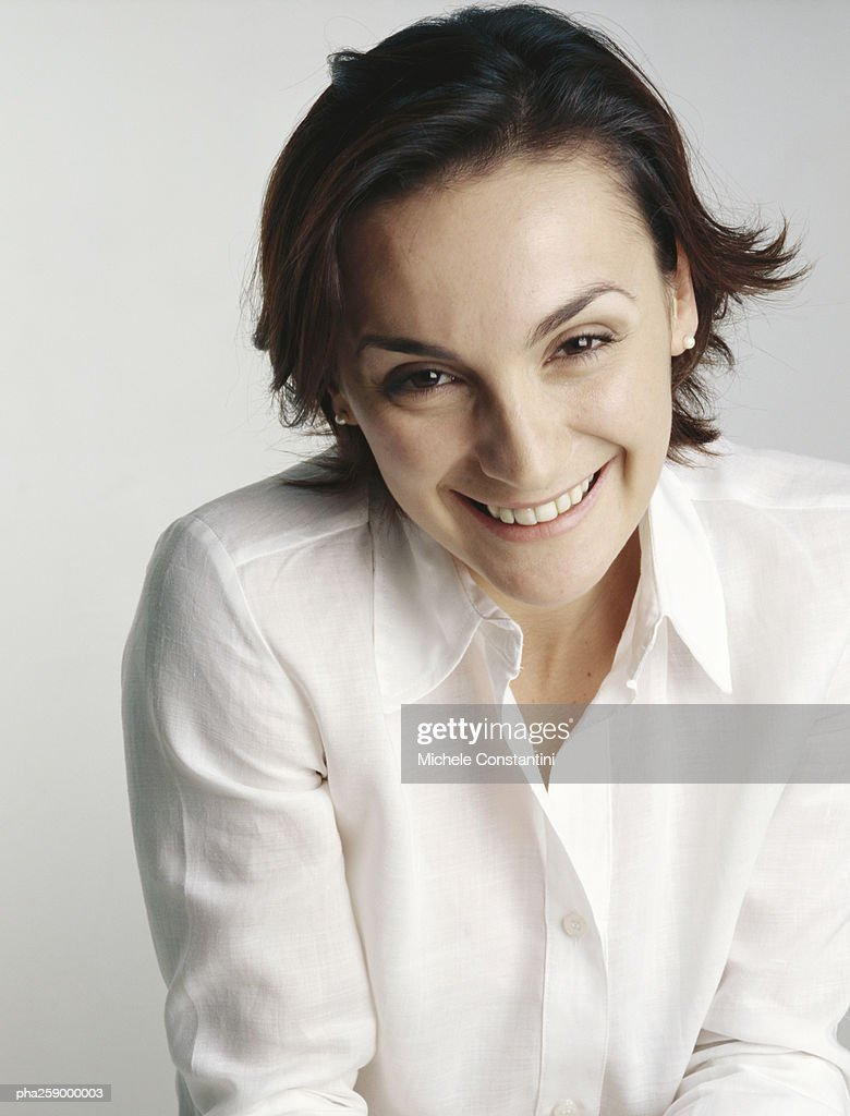 Young woman smiling at camera with eyebrows raised and head slightly tilted forward : Stockfoto