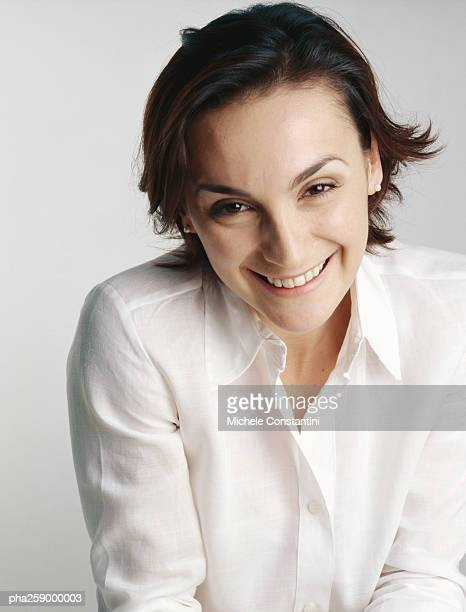 Young woman smiling at camera with eyebrows raised and head slightly tilted forward