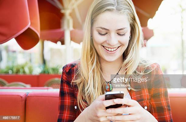 young woman smiling at mobile in cafe