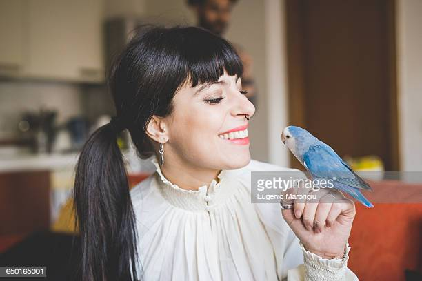 Young woman smiling at pet bird indoors