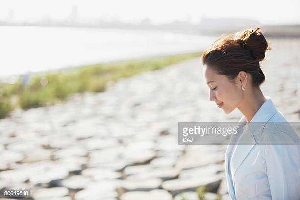 young woman smiling at seaside, differential focus - 下を向く ストックフォトと画像