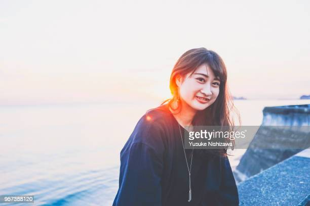 a young woman smiling at the sea - yusuke nishizawa fotografías e imágenes de stock