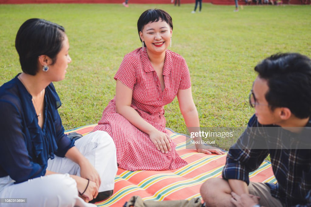 Young woman smiling at two friends while sitting on a mat laid out on the grass : Stock Photo