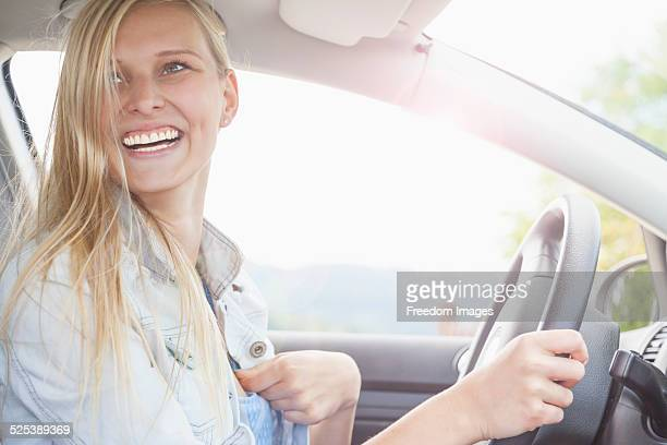 Young woman smiling behind wheel of car