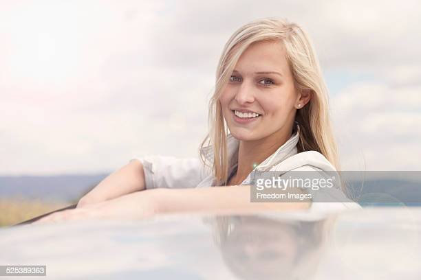 young woman smiling beside car - next to stock pictures, royalty-free photos & images