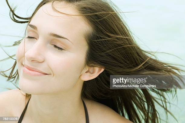 Young woman smiling, eyes closed, hair blowing in breeze, portrait