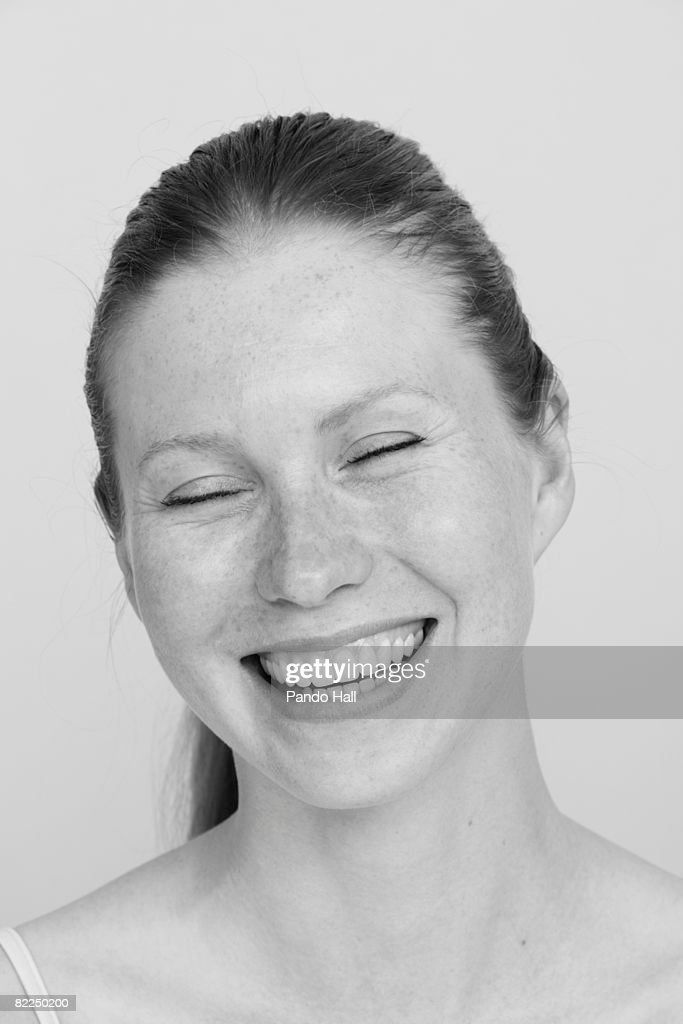 Young woman smiling, eyes closed, portrait : Stock Photo