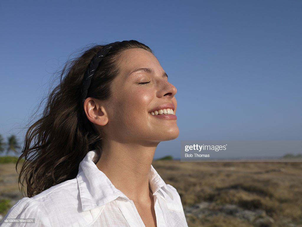 Young woman smiling, eyes closed, side view : Foto stock