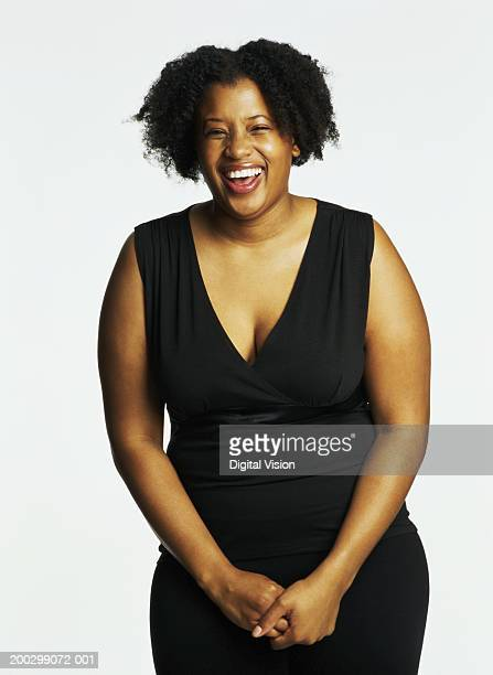 young woman smiling, hands clasped, portrait - images of fat black women stock photos and pictures