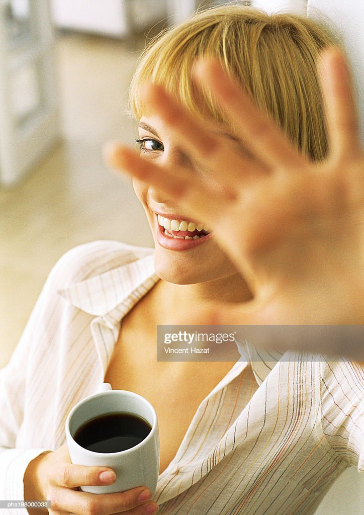 Young woman smiling, head and shoulders, in background, face obscured by hand, blurred, in foreground, high angle view : Stockfoto