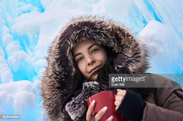 Young woman smiling holding a red cup of tea smiling wearing a parka outside in the cold looking into the camera