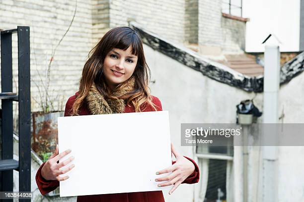 young woman smiling holding blank sign - halten stock-fotos und bilder