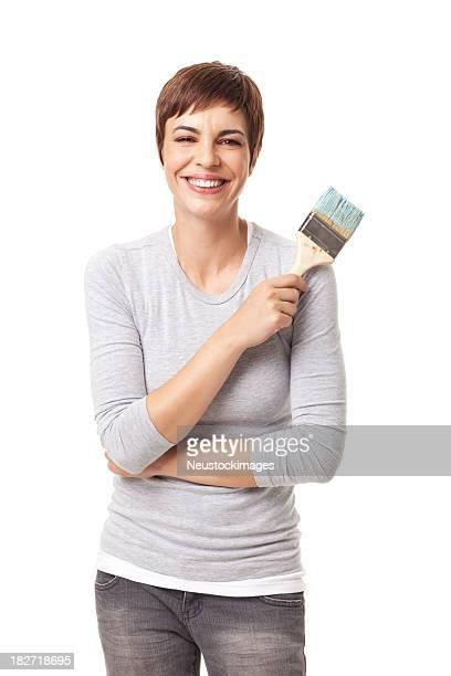 Jeune femme souriante tenant la brosse de peinture isolé en blanc