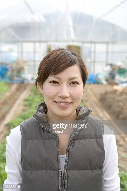 Young woman smiling in a plastic greenhouse