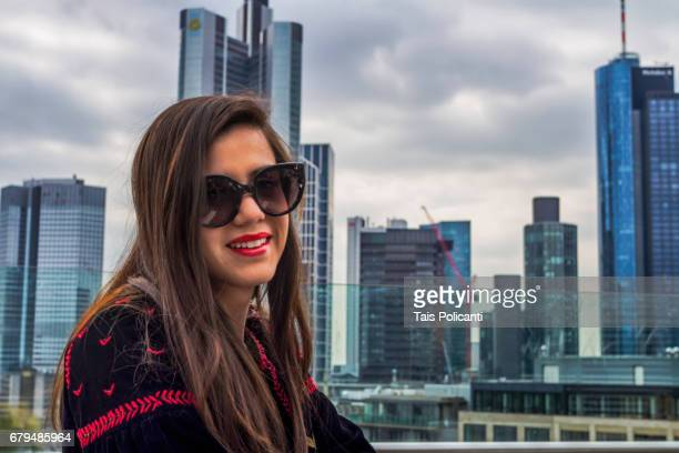 Young woman smiling in a terrace in front the Financial District - Frankfurt, Hessen, Germany