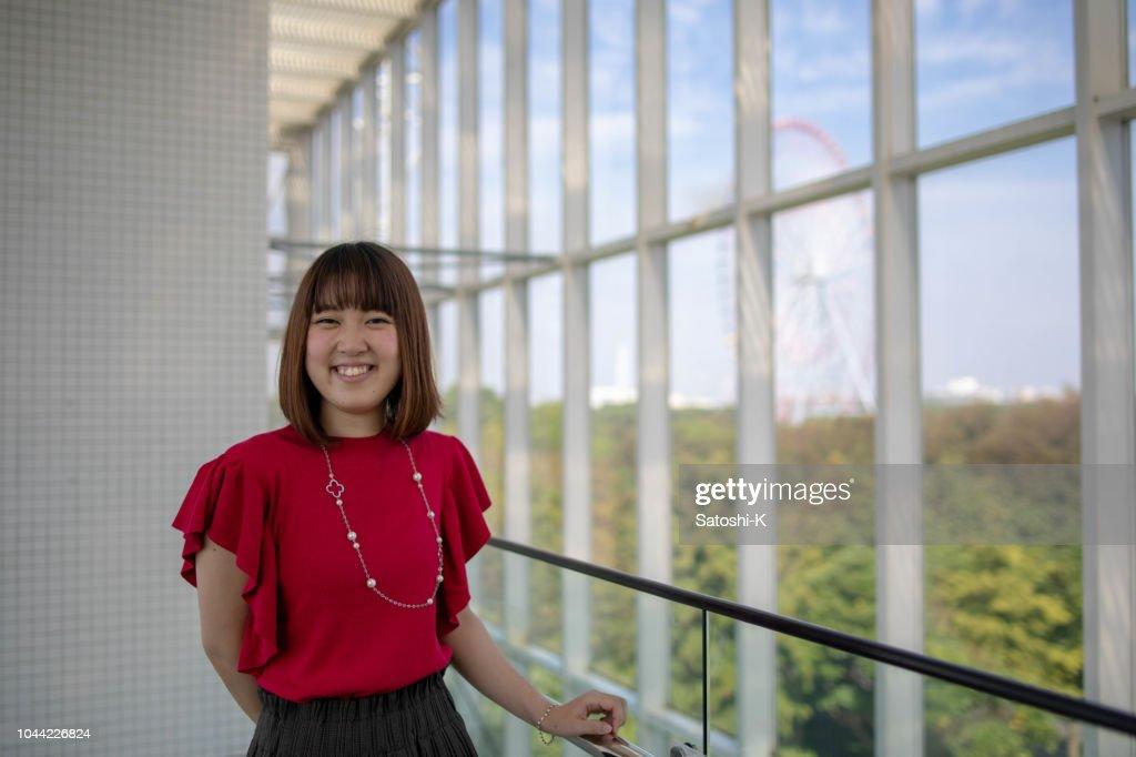 Junge Frau Lächelnd In Gebäude Mit Großem Fenster Stock