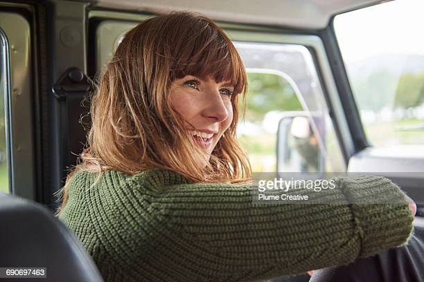 Young woman smiling in car