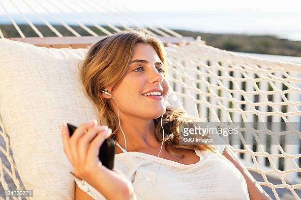 Young woman smiling in hammock listening to headphones
