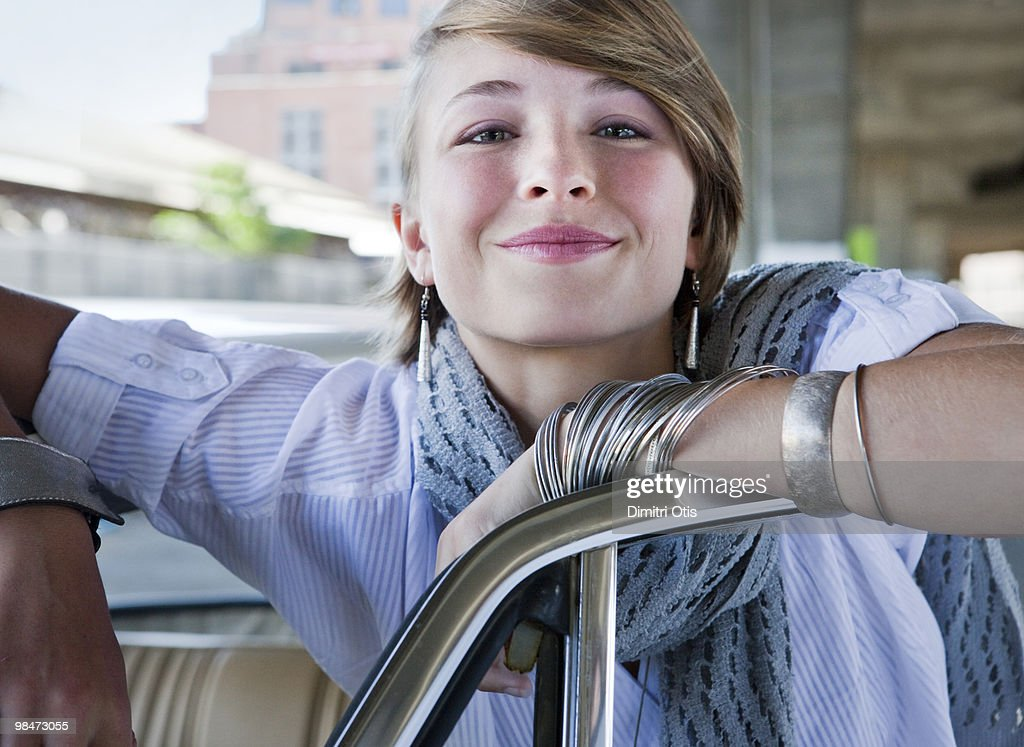 Young woman smiling, leaning on car : Stock Photo
