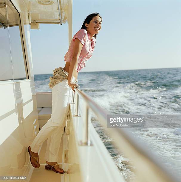 young woman smiling, leaning on railing of boat, looking outwards - もたれる ストックフォトと画像