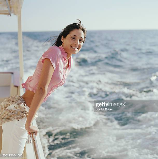 young woman smiling, leaning on railing of boat, portrait - もたれる ストックフォトと画像