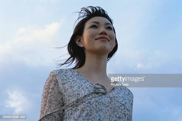 Young woman smiling, looking away, low angle view