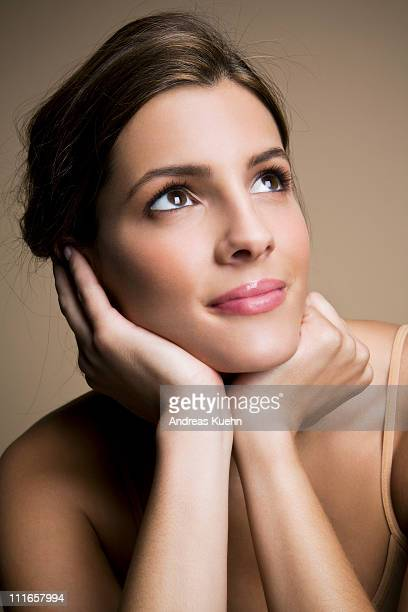 Young woman smiling looking up, portrait.