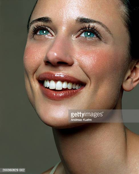 Young woman smiling, looking upwards, close-up