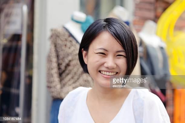 若い女性がいたずらっぽく笑みを浮かべて - ショートヘア ストックフォトと画像