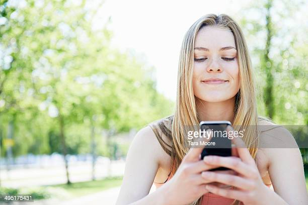 young woman smiling mobile phone in park