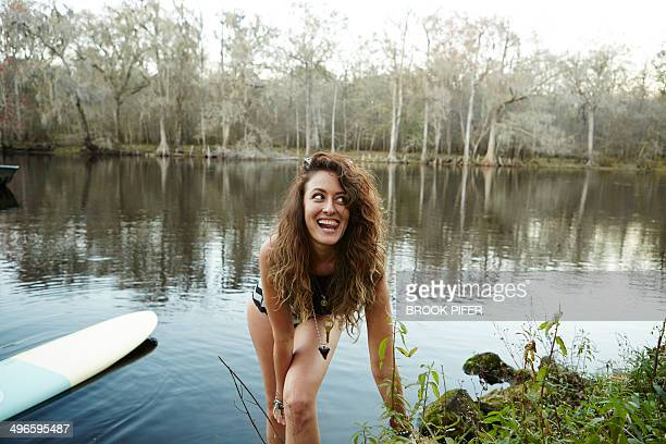 Young woman smiling near water